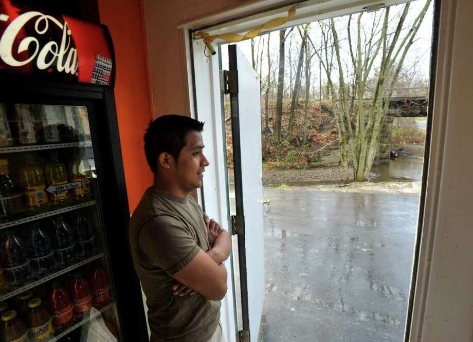 Constancio Garcia, owner of Speedy Pizza located next to the West Street underpass, looks out his doorway, which has a view of the Still River in Danbury on Wednesday, March 28, 2012. Garcia says the river normally floods onto the street around two times a year and he worries about the loss of business due to the recurring flooding in front of his business. Wednesday's rain was the first appreciable for March. Photo: Jason Rearick / The News-Times