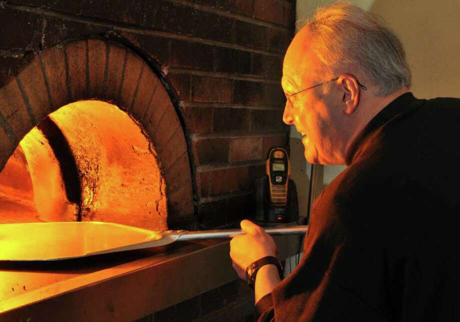 Rocco DeFazio of DeFazio's Pizza at the wood fired oven in his pizzeria on Fourth Street in Troy Wednesday March 14, 2012.    (John Carl D'Annibale / Times Union) Photo: John Carl D'Annibale / 00016810A