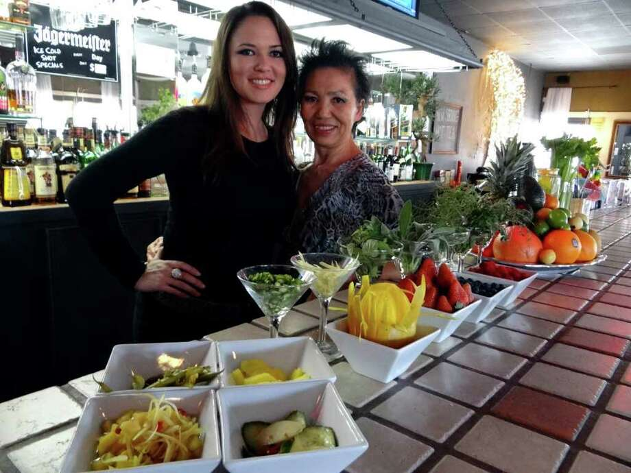 Han Olmstead, right, and her daughter, Marika Olmstead-Wright, serve a variety of pickled fruits and vegetables at Pacific Moon. Tuesday, Jan. 17, 2012. BILLY CALZADA / San Antonio Express-News Photo: BILLY CALZADA, SAN ANTONIO EXPRESS-NEWS / gcalzada@express-news.net