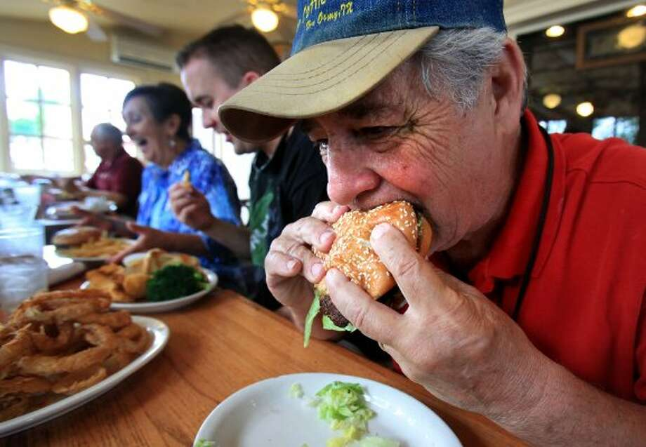 Tony Cadena bites into a hamburger while having lunch with family members at Good Time Charlie's.  Good Time Charlie's is the winner of the inaugural Burger Madness tournament. (Bob Owen / San Antonio Express-News)