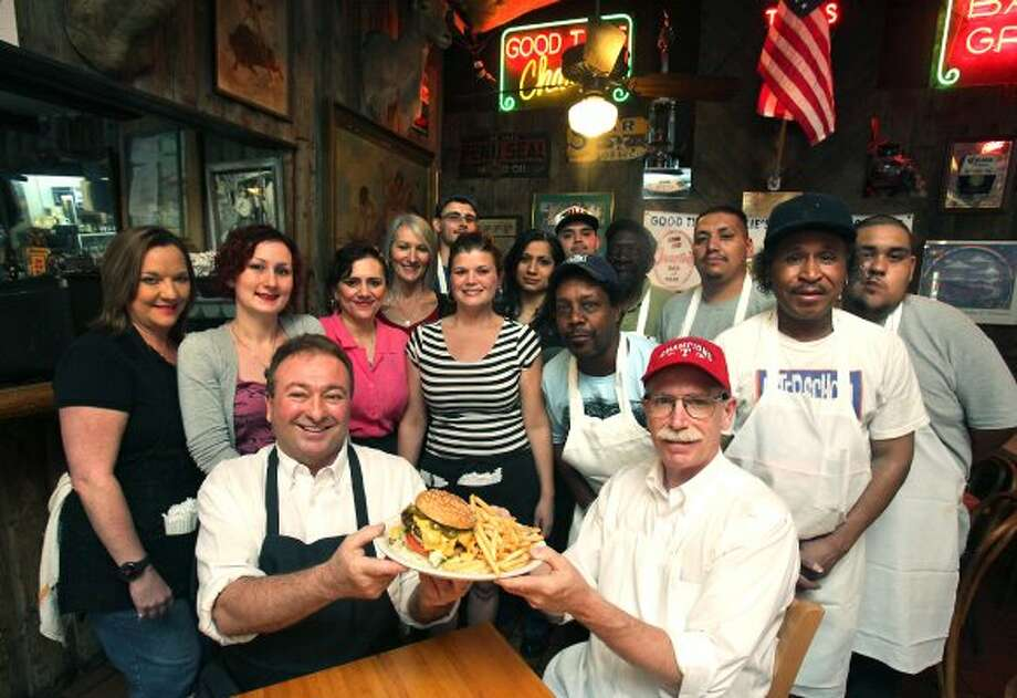 Holding their winning hamburger, Good Time Charlie's co-owners Eddie Ruffo (left) and Millard Stetler are surrounded by the staff of the popular restaurant, which is the winner of the inaugural Burger Madness tournament. (Bob Owen / San Antonio Express-News)