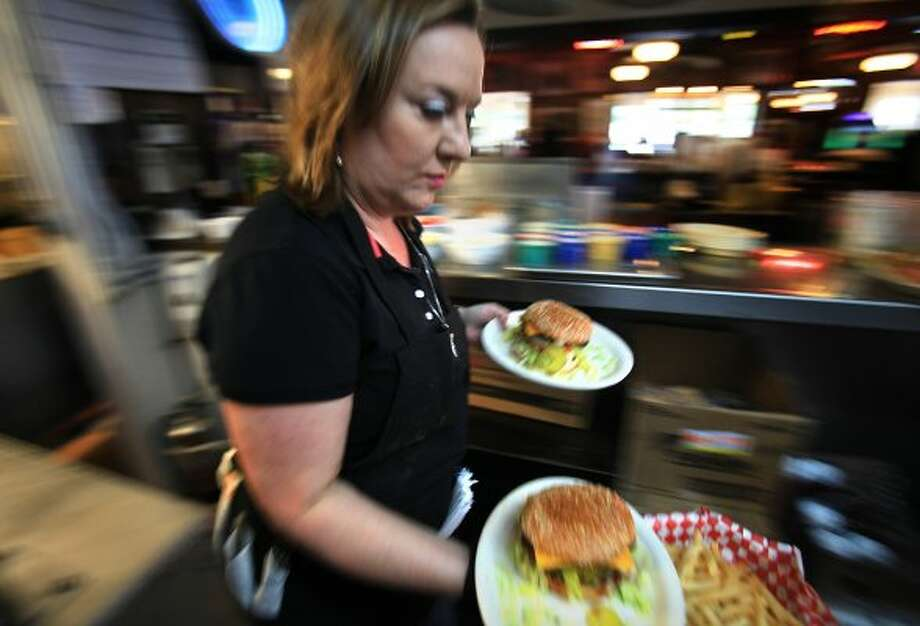 Meg Bennett takes a couple of hamburgers to customers at Good Time Charlie's.  The popular restaurant is the winner of the inaugural Burger Madness tournament.  (Bob Owen / San Antonio Express-News)
