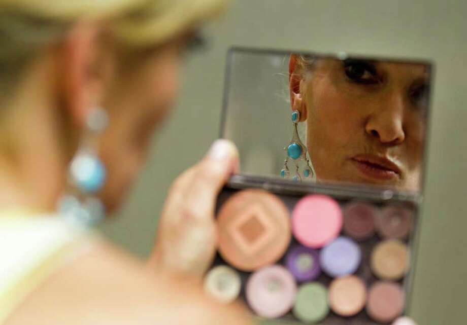 Jana Arnoldy checks her makeup in a small mirror before the annual Houston Chronicle Best Dressed Luncheon Wednesday, March 28, 2012, in Houston. Photo: Brett Coomer, Houston Chronicle / © 2012 Houston Chronicle
