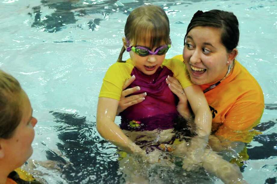 Taylor Brown, organizer of the Friday Knights Fishes, right, swims with Sasha Cherry, 6, on Friday, March 23, 2012, at The College of Saint Rose in Albany, N.Y. The new swim program benefits children with autism. (Cindy Schultz / Times Union) Photo: Cindy Schultz / 00016946A