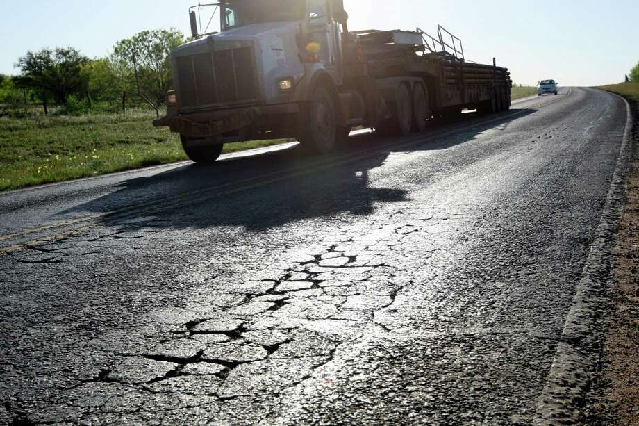 The strain of oil field traffic related to work in the Eagle Ford Shale play is evident on the surface of FM 468 just northwest of Cotulla. Photo: JERRY LARA, San Antonio Express-News / SAN ANTONIO EXPRESS-NEWS