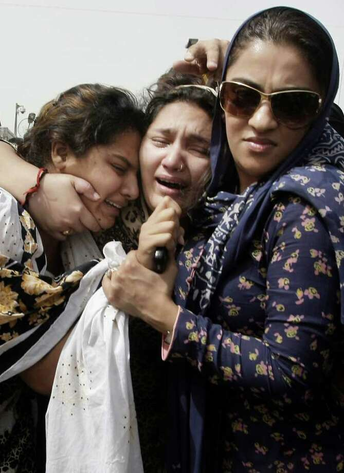 Family members of acid attack victim Fakhra Younus mourn her death in Karachi, Pakistan. Photo: STR / AP