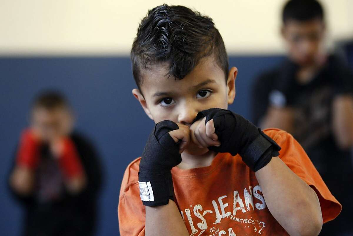 Fernando Carmona age 6 practices hit boxing stance with older boys at the East Oakland Boxing Association, gym. The non-profit organization provides a boxing gym to kids ages 5-20, but also a kitchen and garden and a home environment that provides meals and a safe place to play Thursday March 1, 2012.