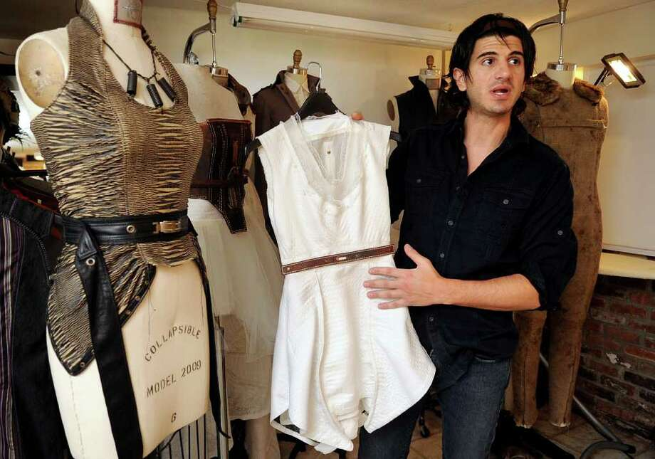 Jason Troisi shows a piece from his fashion line in his Greenwich home on Friday, March 23, 2012. Troisi, a 2010 Project Runway contestant, will be showing a line at an Yves Saint Laurent retrospective in Denver, CO, March 25 to July 8. Photo: Lindsay Niegelberg / Stamford Advocate