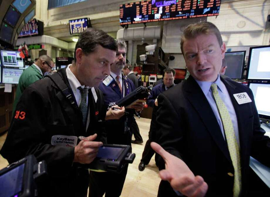 In a Feb. 8, 2012 photo Specialist Michael O'Mara, right, works on the floor of the New York Stock Exchange. U.S. stocks are opening mixed as traders wait for European leaders to hammer out a bailout deal for Greece. U.S. shares were poised for a flat opening Wednes day March 28, 2012 with both Dow futures and the S&P 500 futures up 0.1 percent. (AP Photo/Richard Drew) Photo: Richard Drew