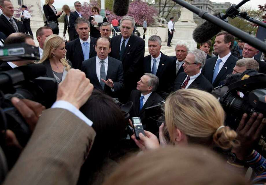 Paul Clement, a lawyer for 26 states seeking to have the Patient Protection and Affordable Care Act tossed out in its entirety, gestures as he speaks to reporters in front of the Supreme Court in Washington, Wednesday, March 28, 2012, at the end of arguments regarding the health care law signed by President Barack Obama. Stand to his left is Florida Attorney General Pam Bondi. (AP Photo/Carolyn Kaster) Photo: Carolyn Kaster / AP