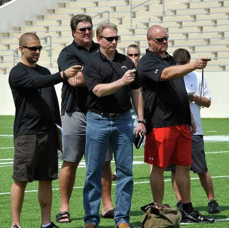 Lamar University Head Football Coach Ray Woodard, second from left, stands behind some of the scouts as they time his players in the 40 yard dash. Lamar University football seniors J.J.Hayes, Darby Jackson, and Marcus Jackson along with others, had a chance to do football-related drills in front of nine National Football League scouts Wednesday afternoon on the playing field. Dave Ryan/The Enterprise