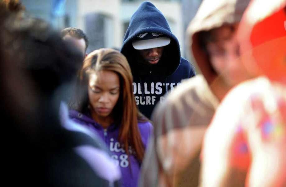 """Seventeen-year-old Romario Henry, of Bridgeport, bows his head in prayer Wednesday, Mar. 28, 2012 during the """"I Am Trayvon Martin Rally,"""" organized by Housatonic Community College student Kirk Wesley on the campus in Bridgeport, Conn. Photo: Autumn Driscoll / Connecticut Post"""