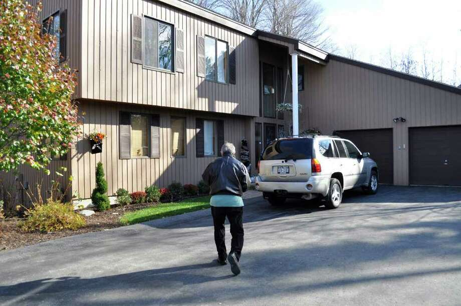 FILE- In this Nov. 18, 2011 file photo, a reporter walks up to former Syracuse University men's basketball associate head coach Bernie Fine's house in DeWitt, N.Y. Fine, who was fired by Syracuse in November 2011, amid allegations he sexually molested two former ball boys, has put the house on the market. The asking price is $549.900. (AP Photo/Kevin Rivoli, File) Photo: Kevin Rivoli