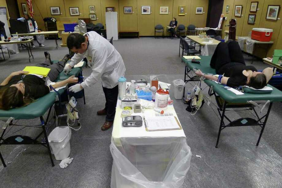 American Red Cross Donor Specialist Patrick Burns, left, takes care of a doner during a blood drive at the William Sanford Library in Colonie N.Y., Tuesday March 27, 2012. (Michael P. Farrell/Times Union) Photo: Michael P. Farrell / 00016966A