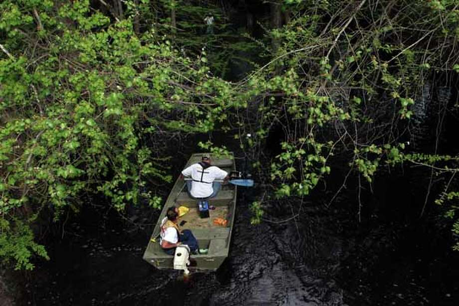 Texas Equusearch used a small boat equipped with sonar to search for 2-year-old Devin Davis in a creek near his home where he went missing yesterday afternoon while his mother was taking a nap in Liberty County east of Cleveland Wednesday, March 28, 2012, in Cleveland.  The boy's mother said she had fallen asleep after securing her son and another 1-year-old child for a nap, said Rex Evans with the Liberty County Sheriff's Department. The mother told authorities that the door to the house was locked with a bolt, but somehow the child managed to get outside. She discovered him missing about 3:30 p.m. Tuesday, looked around frantically for a while and then alerted authorities who issued an Amber Alert. Evans said the mother also found the door to her jeep was ajar, though she said she had left it shut. The child was last seen wearing a red and gray T-shirt and jeans. Initially, authorities thought he was wearing Spiderman tennis shoes but those shoes were located inside the home. Photo: Johnny Hanson, Houston Chronicle / © 2012  Houston Chronicle