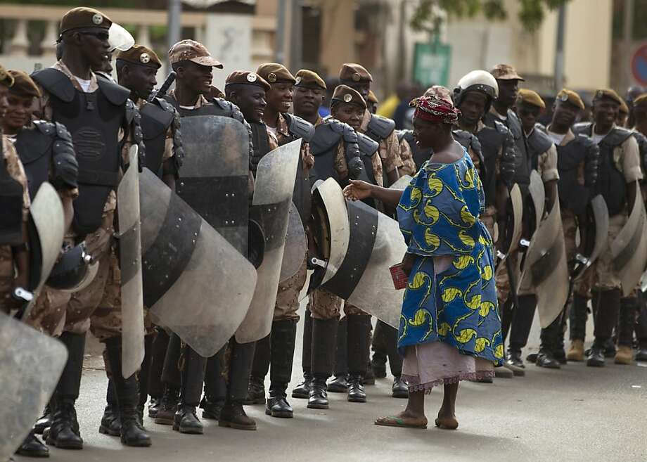 A woman talks with security forces providing security for a march in support of a recent military coup, in Bamako, Mali Wednesday, March 28, 2012. The body representing nations in western Africa has suspended Mali and has put a peacekeeping force on standby in the most direct threat yet to the junta that seized control of this nation in a coup last week.(AP Photo/Rebecca Blackwell) Photo: Rebecca Blackwell, Associated Press