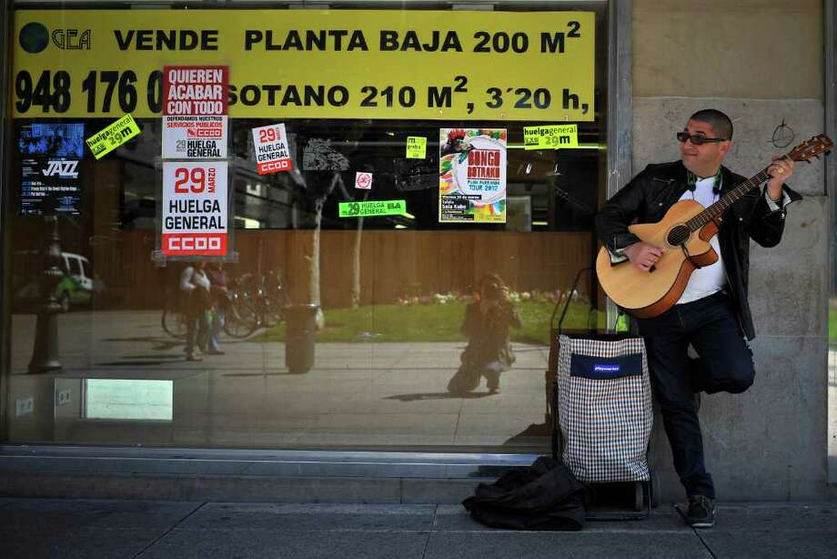 A street musician in Pamplona plays Wednesday beside a closed shop displaying posters announcing a general strike protesting against the Spanish government's cutbacks and changes in labor rules. Photo: Alvaro Barrientos / AP