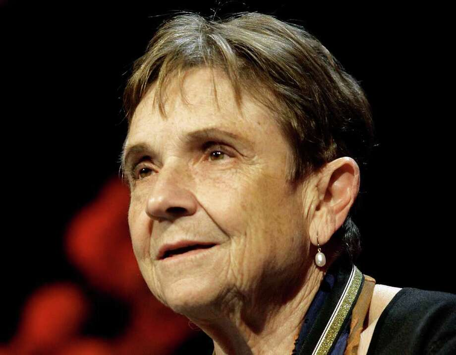 FILE - In this Nov. 15, 2006 file photo, poet Adrienne Rich addresses dinner guests after receiving the Medal for Distinguished Contribution to American Letters at the 2006 National Book Awards sponsored by The National Book Foundation in New York. Rich, whose socially conscious verse influenced a generation of feminist, gay rights and anti-war activists, has died. She was 82.  Rich, who had lived in Santa Cruz since the 1980s, died Tuesday, March 27, 2012 at her home. Her son, Pablo Conrad, says she died of complications from rheumatoid arthritis. (AP Photo/Stuart Ramson, file) Photo: STUART RAMSON