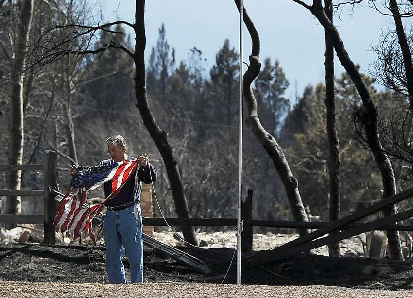 DENVER, CO - MARCH 28: A man saves a scorched flag from a home destroyed by the Lower North Fork Fire March 28, 2012 in Conifer, Colorado. They are part of the State Wildland Inmate Fire team. The fire which has burned 4,500 acres has claimed two lives and over 20 homes. (Photo by Chris Schneider/Getty Images)