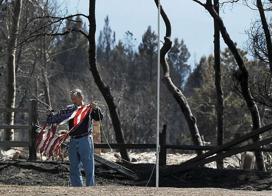 DENVER, CO - MARCH 28:  A man saves a scorched flag from a home destroyed by the Lower North Fork Fire March 28, 2012 in Conifer, Colorado. They are part of the State Wildland Inmate Fire team. The fire which has burned 4,500 acres has claimed two lives and over 20 homes. (Photo by Chris Schneider/Getty Images) Photo: Chris Schneider, Getty Images