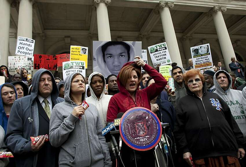NEW YORK, NY - MARCH 28: New York City Council Speaker Christine Quinn (C) puts on a hoodie as she speaks during a press conference to call for justice in the February 26 killing of 17-year-old Trayvon Martin in Sanford, Florida, on the steps of City Hall March 28, 2012 in New York City. Martin was killed by George Michael Zimmerman while on neighborhood watch patrol in the gated community of The Retreat at Twin Lakes. (Photo by Allison Joyce/Getty Images) *** BESTPIX ***