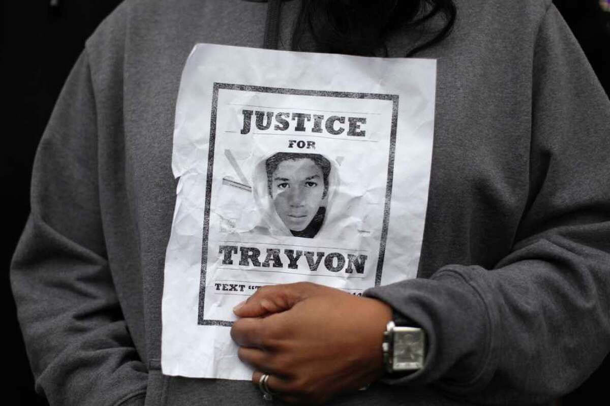 A woman holds an image of Trayvon Martin during a protest calling for justice in the killing of Martin, a young African-American teenager shot and killed by a neighborhood watch captain in Florida. The gathering at Westlake Park in Seattle drew hundreds of people on Wednesday, March 28, 2012.