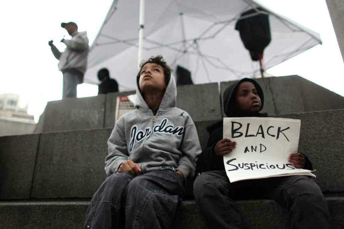 Jesus Lewis, 7, left, and Abdul Kebbeh, 5, participate in a protest calling for justice in the killing of Trayvon Martin, a young African-American teenager shot and killed by a neighborhood watch captain in Florida. The gathering at Westlake Park in Seattle drew hundreds of people on Wednesday, March 28, 2012.