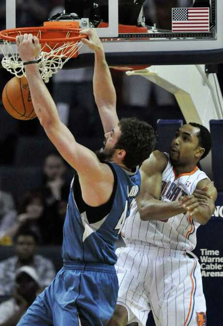 The Wolves' Kevin Love, left, scores two of his 40 points in Wednesday night's win over the Bobcats. Photo: Robert Lahser / Charlotte Observer