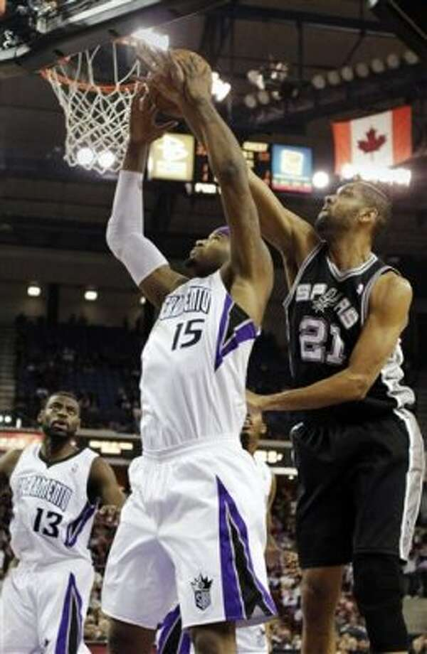 Sacramento Kings center DeMarcus Cousins, center, tries to pull down a rebound against San Antonio Spurs forward Tim Duncan during the first quarter of an NBA basketball game in Sacramento, Calif., Wednesday, March 28, 2012. (AP Photo/Rich Pedroncelli) (AP)