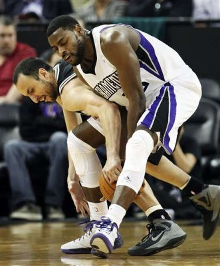 San Antonio Spurs forward Manu Ginobili, of Argentina, left, and Sacramento Kings guard Tyreke Evans scramble for the ball during the first quarter of an NBA basketball game in Sacramento, Calif., Wednesday, March 28, 2012. (AP Photo/Rich Pedroncelli) (AP)