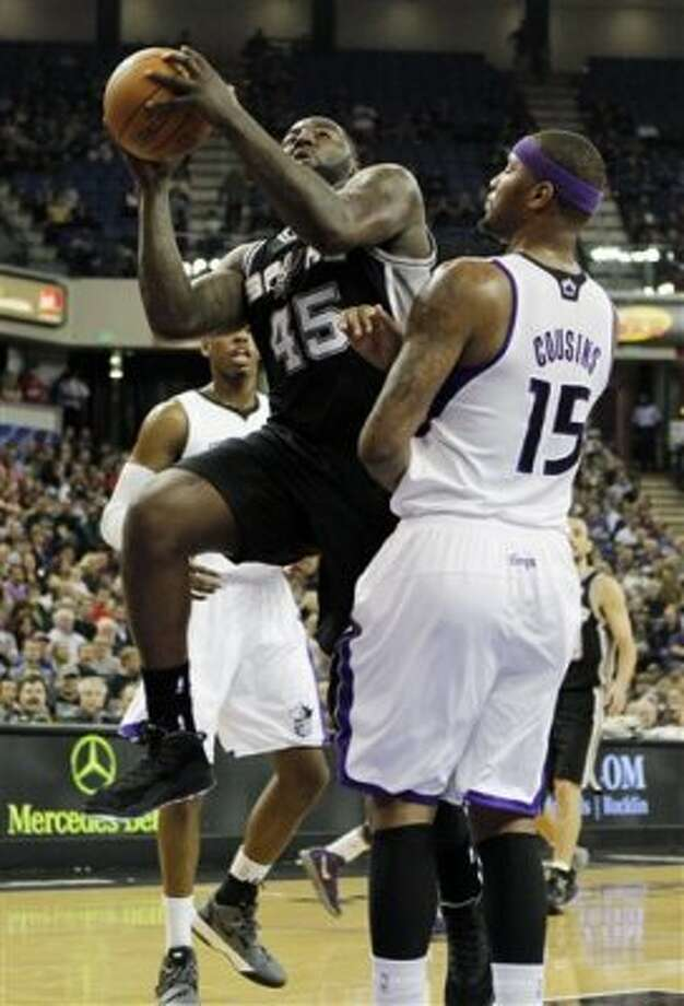 San Antonio Spurs' DeJuan Blair, left, goes to the basket against Sacramento Kings center DeMarcus Cousins during the first quarter of an NBA basketball game in Sacramento, Calif., Wednesday, March 28, 2012. (AP Photo/Rich Pedroncelli) (AP)