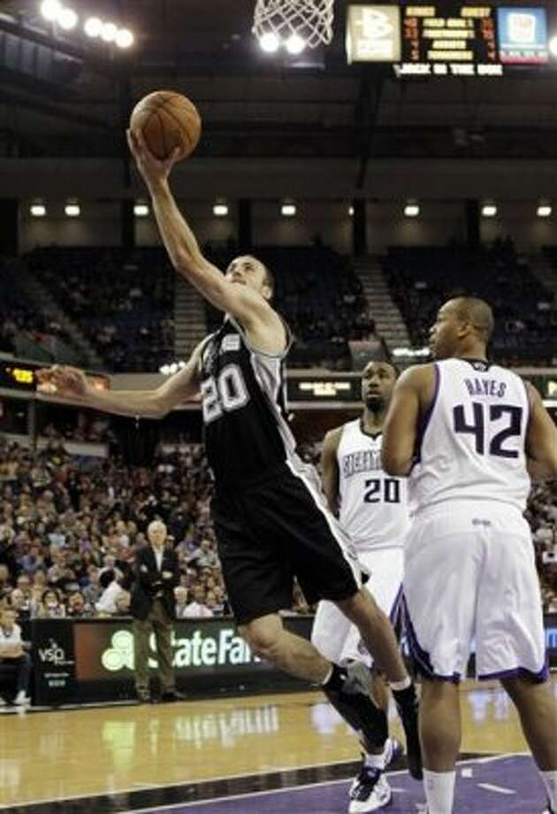 San Antonio Spurs forward Manu Ginobili, of Argentina, left, leans in for the layup past Sacramento Kings' Donte Greene, center, and Chuck Hayes during the first quarter of an NBA basketball game in Sacramento, Calif., Wednesday, March 28, 2012. (AP Photo/Rich Pedroncelli) (AP)