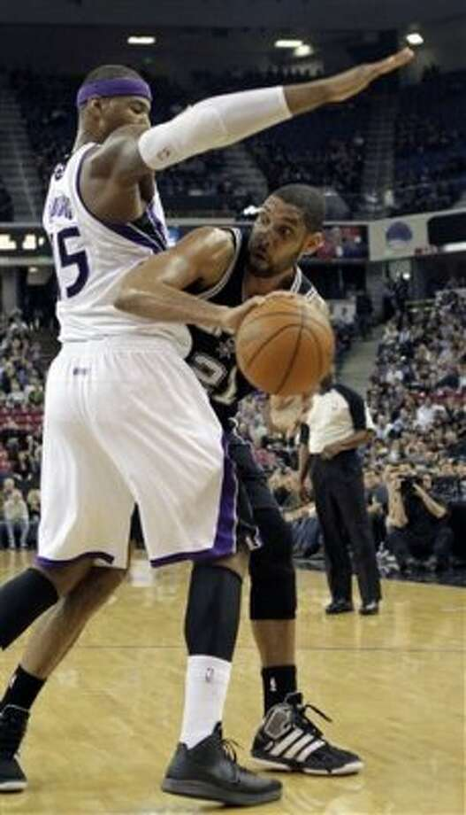 San Antonio Spurs forward Tim Duncan, right, leans around Sacramento Kings center DeMarcus Cousins to make a pass  during the first quarter of an NBA basketball game in Sacramento, Calif., Wednesday, March 28, 2012. (AP Photo/Rich Pedroncelli) (AP)