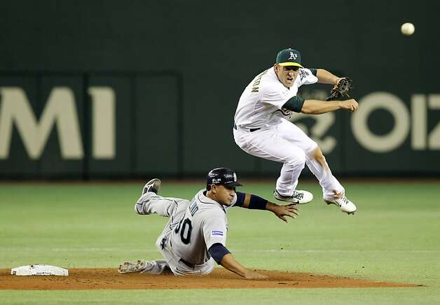 Oakland Athletics shortstop Cliff Pennington throws to make a double play as Seattle Mariners' Miguel Olivo slides in the fifth inning of their American League season opening MLB baseball game at Tokyo Dome in Tokyo, Wednesday, March 28, 2012. Photo: Koji Sasahara, Associated Press