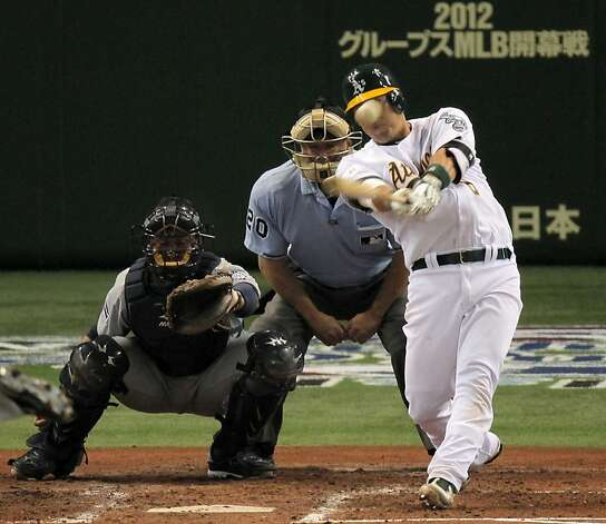 Oakland Athletics' Kurt Suzuki hits an RBI double as Seattle Mariners catcher Miguel Olivo looks on in the fourth inning of their American League season opening MLB baseball game at Tokyo Dome in Tokyo, Wednesday, March 28, 2012. Photo: Itsuo Inouye, Associated Press