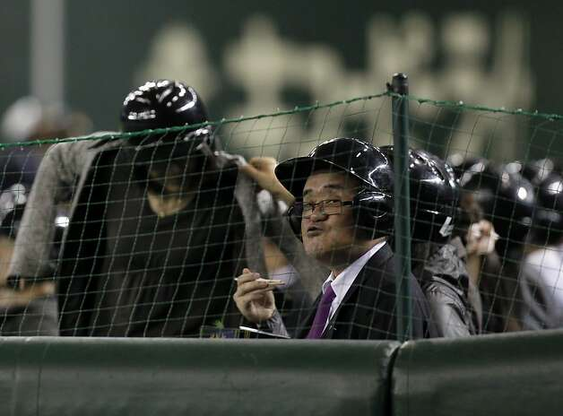 A helmeted fan eats at the premium seats as he watches the American League season opening MLB baseball game between the Oakland Athletics and the Seattle Mariners at Tokyo Dome in Tokyo, Wednesday, March 28, 2012. Photo: Koji Sasahara, Associated Press