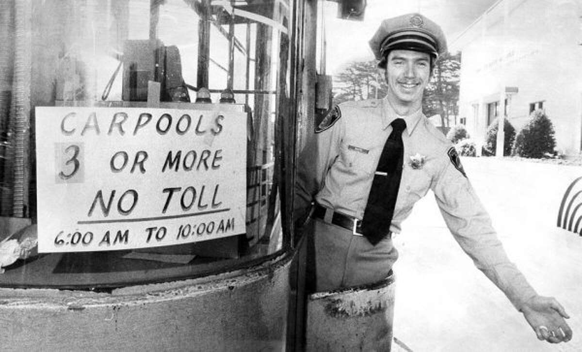 April 13, 1976: Toll collector Bill McKeon -- wearing what looks like a Mayberry issue uniform -- stands next a carpool lane sign on the Golden Gate Bridge. (Clem Albers / The Chronicle)