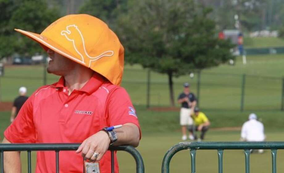 Michael Smith of Beaumont wears a Puma promotional cap which has professional golfers' autographs as he and his friends watch the Shell Houston Open Pro-Am tournament on Wednesday morning. (Nick De La Torre / Houston Chronicle)