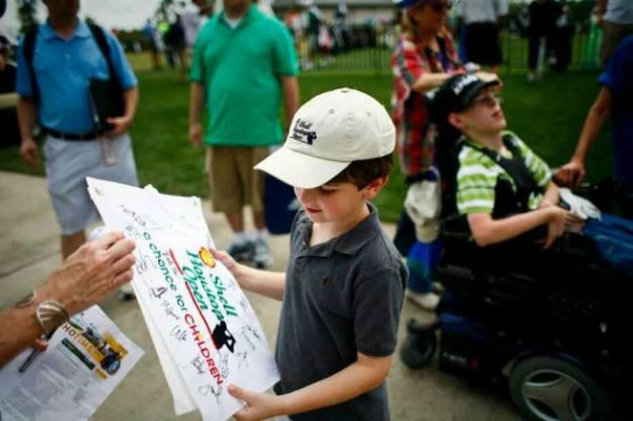 Kyle Clouse, 7, of Kingwood, looks at he autographs he's collected as he visits the Shell Houston Open, Tuesday, March 27, 2012, at the Redstone Golf Club in Humble.  (Nick De La Torre / Houston Chronicle)