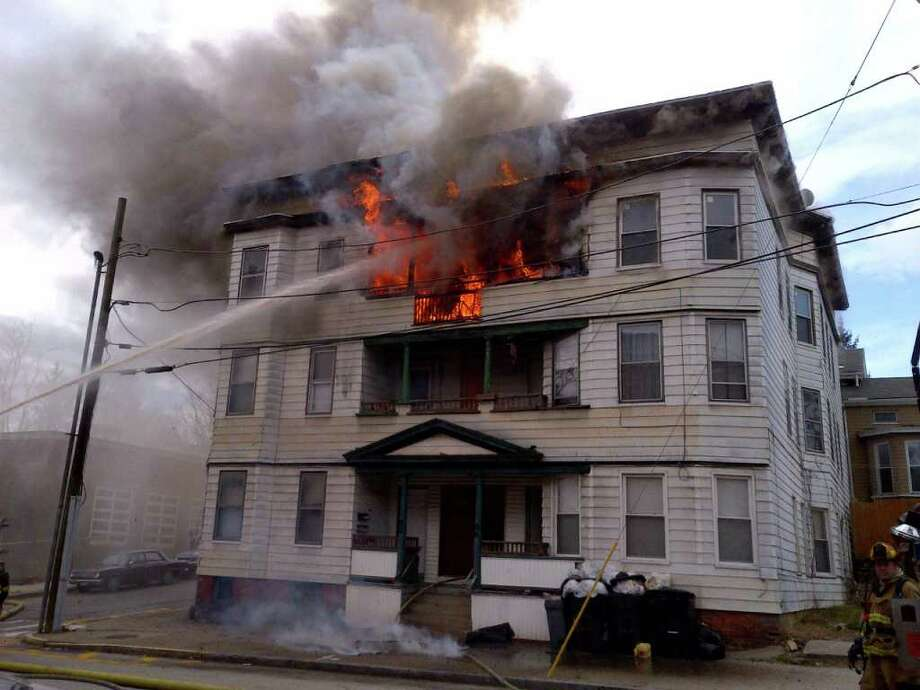 A fire swept through a Derby apartment building early Thursday afternoon, Marcy 29, 2012 with several fire departments responding with mutual aid. All of occupants living in the six-family building escaped upharmed. Photo: Ellen Lenart