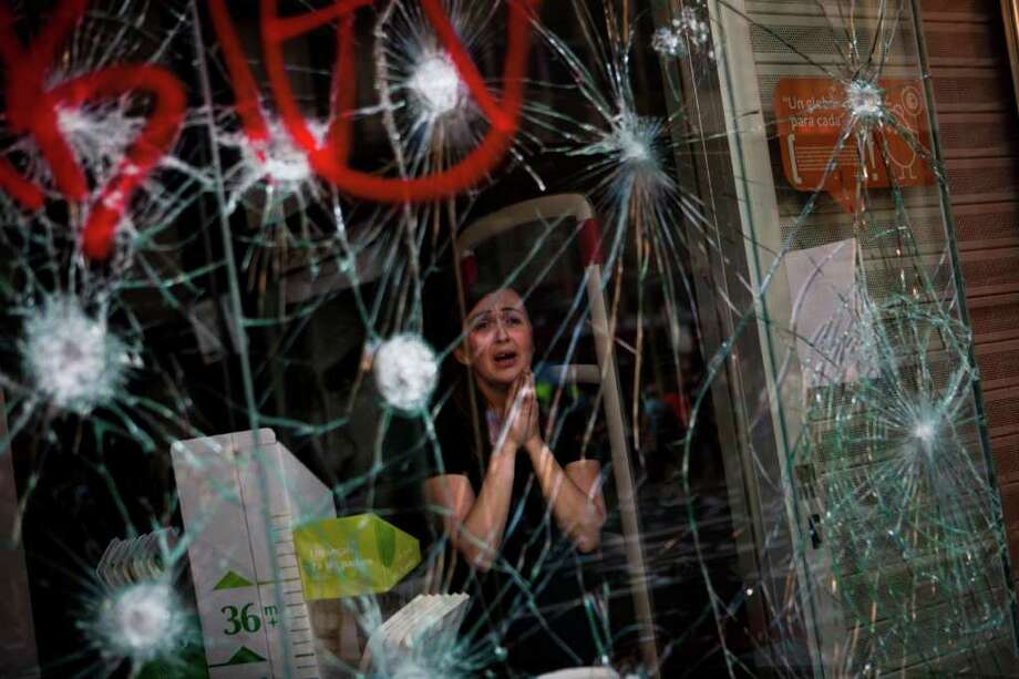 Mirian Burrueco, 30, reacts behind the broken glass of her shop stormed by demonstrators during clashes at the general strike in Barcelona, Thursday, March 29, 2012. Spanish workers livid over labor reforms they see as flagrantly pro-business staged a nationwide strike Thursday and tried to bring the country to a halt by blocking traffic, closing factories and clashing with police in rowdy demonstrations. (AP Photo/Emilio Morenatti) Photo: Emilio Morenatti, Associated Press / AP