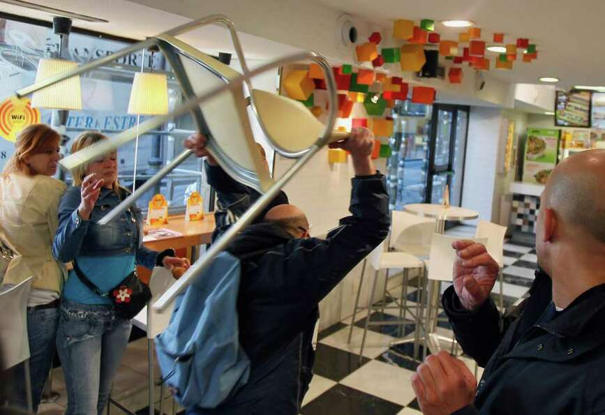 A protester throws a chair inside a food shop in Madrid Thursday, March 29, 2012 during a general st