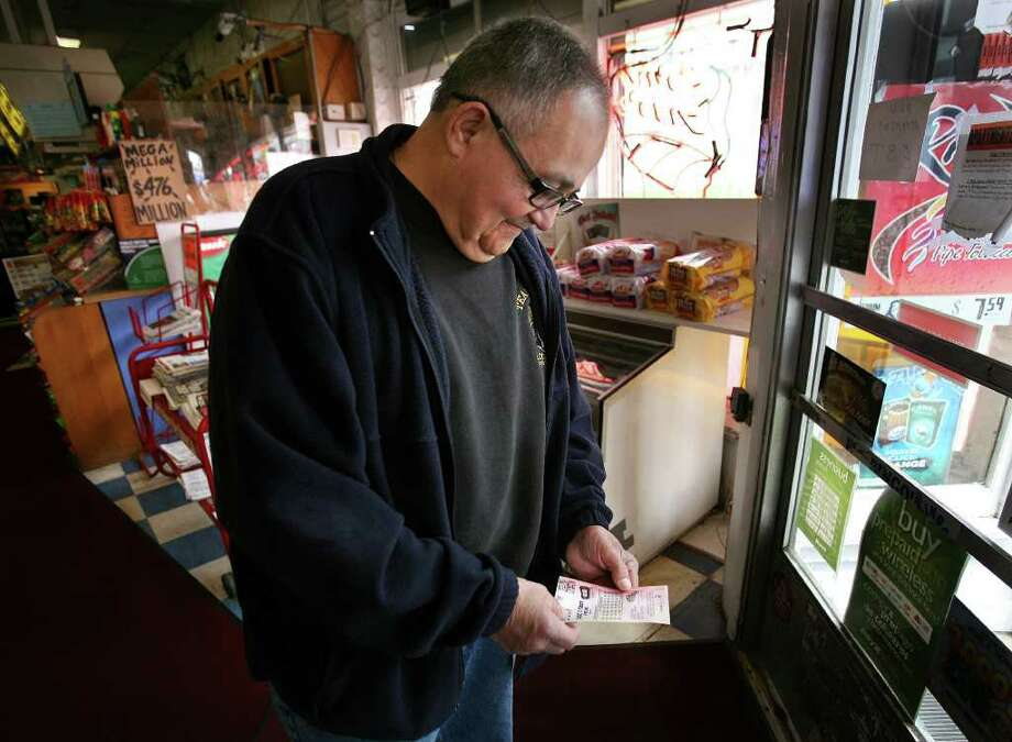 Pedro Vega of Stratford looks at his ticket numbers after purchasing five entries in the Megamillions lottery at Martin's News on Barnum Avenue in Bridgeport on Thursday, March 29, 2012. Photo: Brian A. Pounds / Connecticut Post