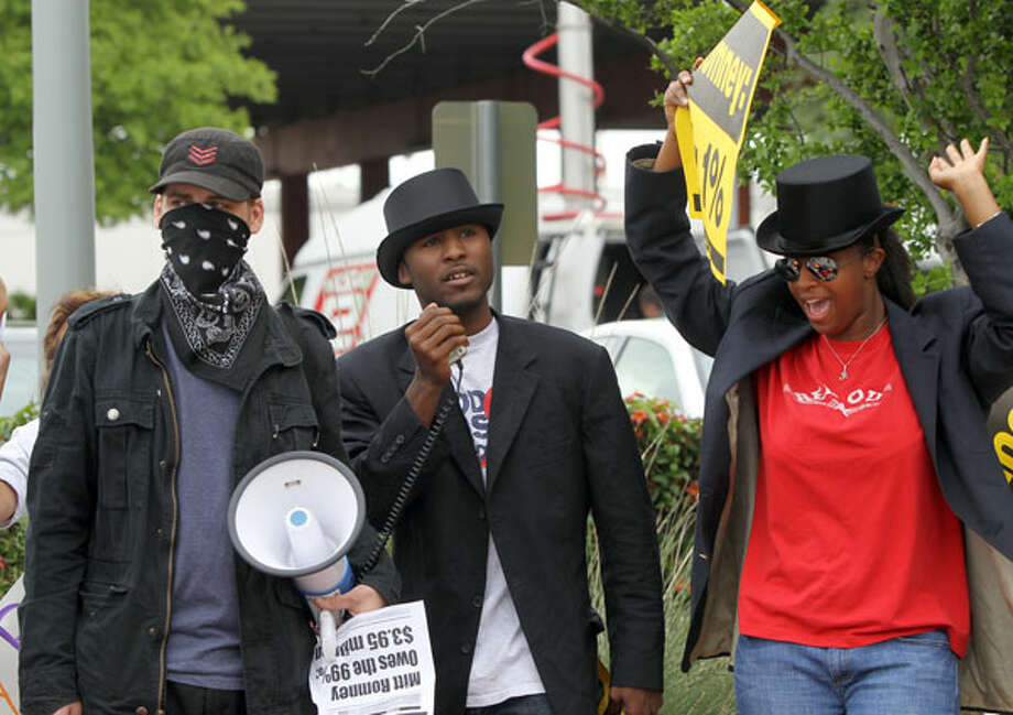 Protesters Freddy Frederickson (from left), Daniel Jefferson and Devin Nixon protest at the Pearl Stable while Republican presidential front-runner Mitt Romney visits San Antonio for a fundraiser. Photo: John Davenport, San Antonio Express-News