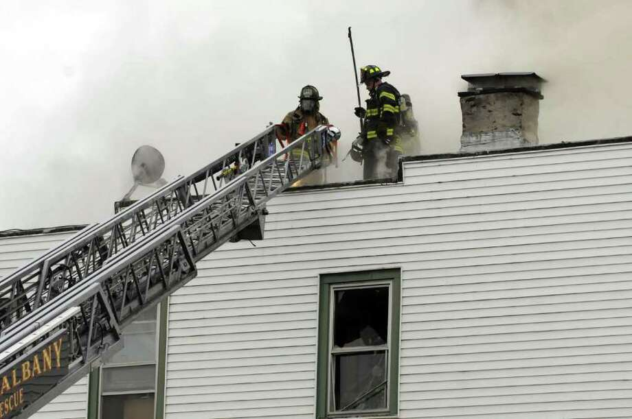 Firefighters work a fire at 69 and 71 Watervliet Avenue in Albany N.Y., Thursday March 29, 2012. (Michael P. Farrell/Times Union) Photo: Michael P. Farrell