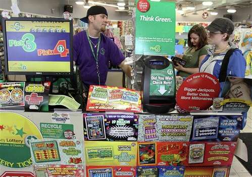 Brad Hartzell, left,  of Somers Point, sells lottery tickets to Lisa Lysinger, of Ocean City, at a A Few Bucks store, Wednesday, March 28, 2012 in Somers Point, N.J. (AP Photo/The Press of Atlantic City, Dale Gerhard) (AP)