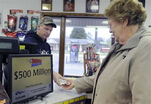 Lavery's Convenience Store owner Bill Lavery, left, hands Mega Millions lottery tickets to customer Virginia Kuhn, Thursday,  March 29, 2012 in Waterford, Pa. (AP Photo/Erie Times-News, Greg Wohlford)  TV OUT; MAGS OUT; COMMERCIAL INTERNET OUT (AP)