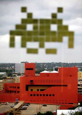 A Space Invaders alien made of sticky notes posted on a window, appears, Tuesday March 27, 2012, to be landing on the San Antonio Public Library as seen from the 11th floor offices at Geekdom, the San Antonio-based collaborative workspace for tech enthusiasts. Photo: William Luther, San Antonio Express-News / © 2012 WILLIAM LUTHER