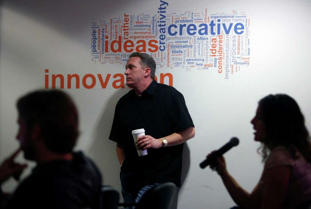 Geekdom director Nicholas Longo, center, listens to tech start-up companies as they make practice pitches in advance of pitching their ideas to real investors in April 11.