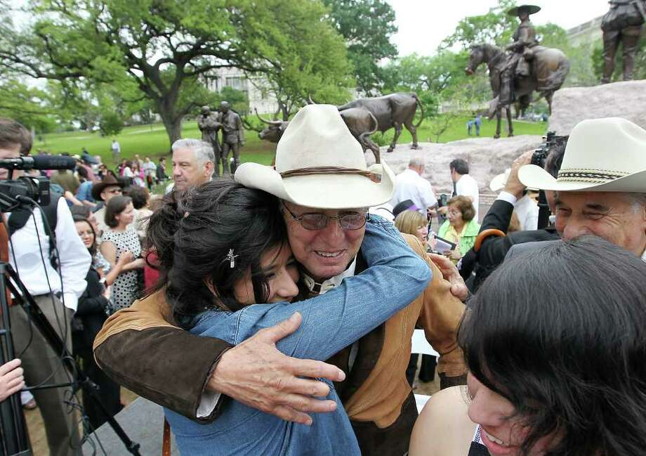 Artist and sculptor Armando Hinojosa, who designed the Tejano Monument, gets a hug from former student Diana Lopez of Laredo after the monument's dedication at the Texas Capitol in Austin on Thursday, March 29, 2012. Photo: Kin Man Hui, San Antonio Express-News / ©2012 San Antonio Express-News